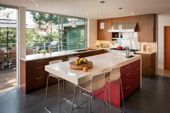 An image of a sleek modern kitchen, with a wide window and sliding door that open entirely on the deck beyond