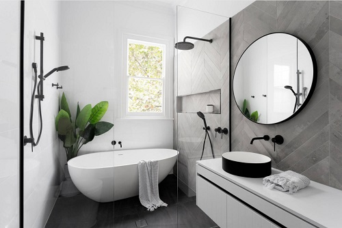 A photo of a modern in-shower bathtub with a smooth egg shape and high-contrast matte black hardware