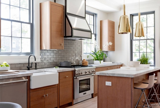 An image of a warm wood kitchen with mixed metallic hardware and a high-powered range hood