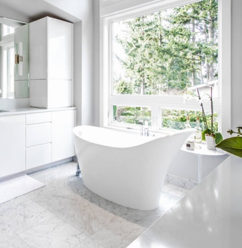 A photo of a modern slipper tub in a bright white bathroom filled with natural light and a view of a forest outside