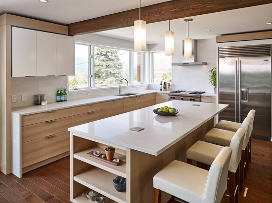 A photo of a modern wood and white quartz kitchen, which has outlets built into the surface of the kitchen island