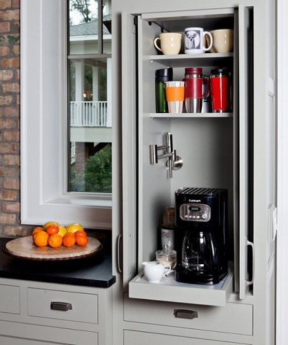 A photo of an open kitchen cabinet. Inside is a coffee pot and fixings, coffee mugs, and a built-in pot filler to supply the water