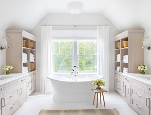A photo of a traditional pedestal-style bathtub with a claw filler in a brightly lit transitional bathroom