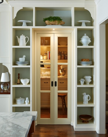 An image of a butler's pantry seen from the outside, beyond the closed French-doors. The space is lit cozily, with hints of baking supplies visible but indistinct