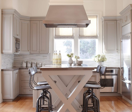 An image of a petite gray kitchen with high-backed industrial-style bar chairs