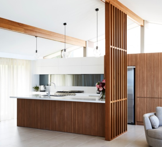 A photo of a modern white and walnut kitchen, with a slatted ceiling-height divider between the kitchen and living room