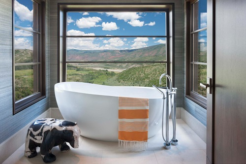 A photo of a petite freestanding bathtub with a matching filler, in a tub niche with a panoramic view of the Colorado mountains