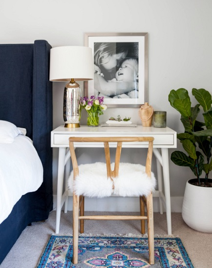 A close up of a vintage wishbone chair with a lambskin seat cover, in front of a desk clearly occupying the space of a nightstand beside a blue-upholstered bed frame