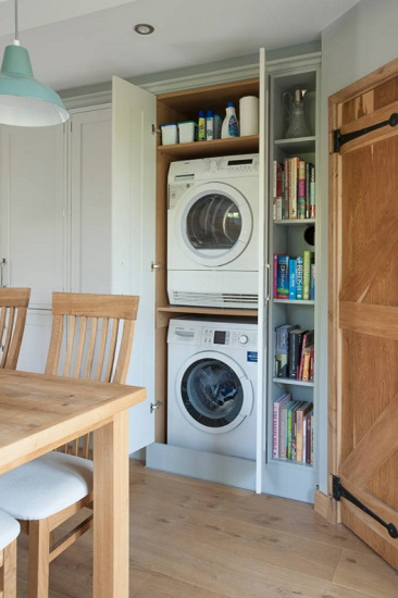 An image of a stacked washer and dryer combo housed in a closet conversion in a kitchen or dining room