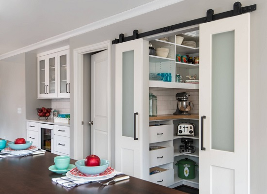 An image of a large walk-in pantry recessed into the wall of the kitchen, borrowing closet space from the adjacent room