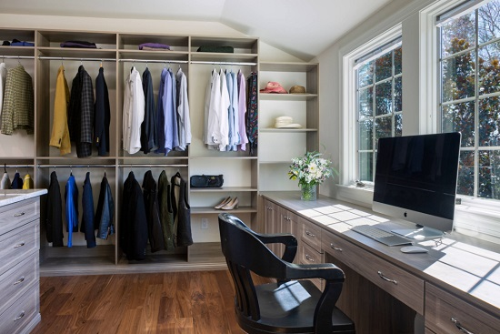 A photo of a large, well-lit walk-in closet with a large built in desk