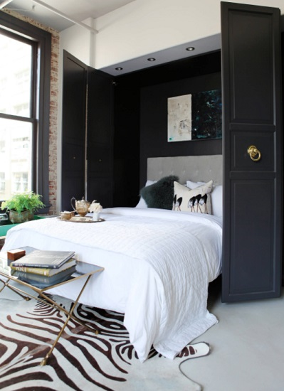 An image of a Murphy bed unfolded out from a chic black-painted closet