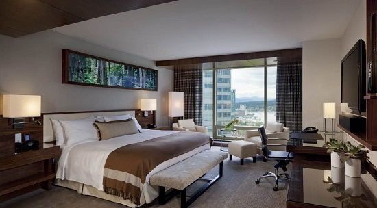 An image of a luxury hotel suite from the Fairmont hotel in Vancouver, featuring a king bed, desk, television, and small reading area