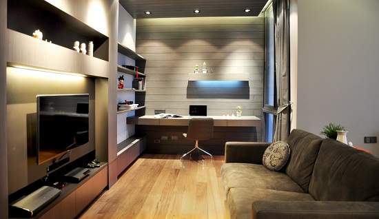 An image of a moodily-lit family room with a home theater setup along one side and a home office against the far wall