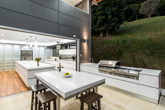An image of an outdoor grill and dining area looking into a brightly-lit kitchen through a wide opening where the glass wall has been folded out of the way