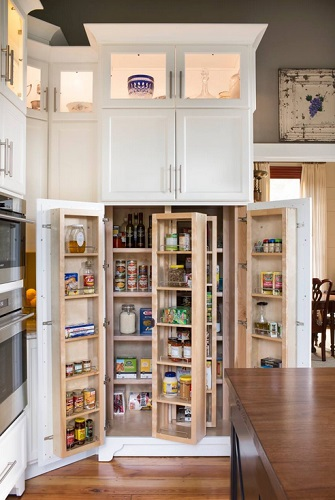 An image of a kitchen pantry with the doors opened, revealing may movable shelves inside