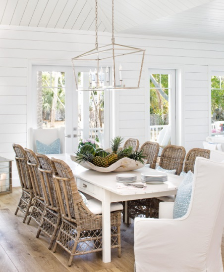 An image of an airy farmhouse dining table with shiplap walls, wicker furniture, and a brushed silver lantern light above the table