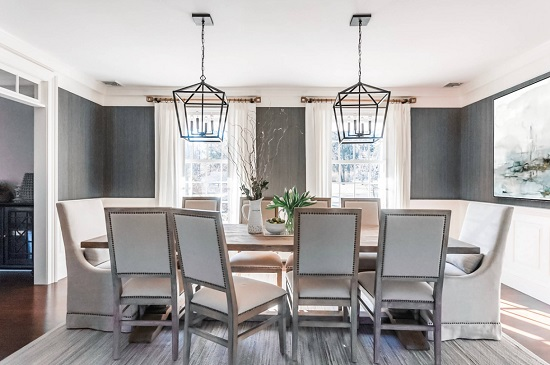A long dining room lit by a matching pair of black-framed lantern lights