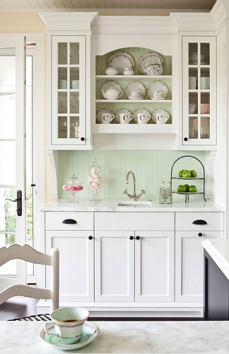 An image of a small prep station with a traditional cottage feel, decorated with a tea set displayed on open shelves above a small sink