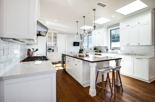An image of a brightly lit white kitchen, with several different types of visible lighting fixtures