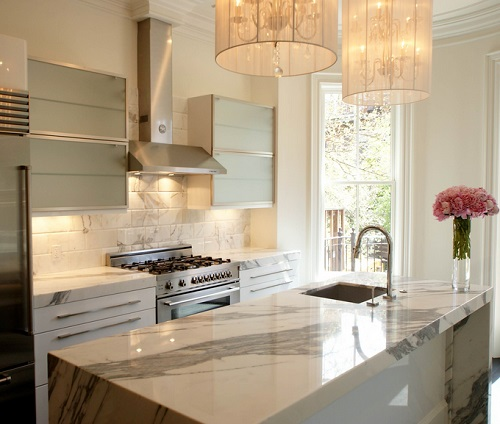 An image of a small white-and-marble kitchen lit by a low light from under the range hood and surrounding cabinets