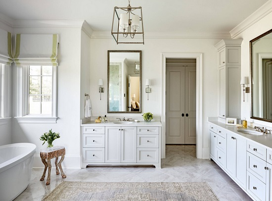 An image of a large white bathroom. The walls are lined with scocnes, and the room is topped with a matching chandelier