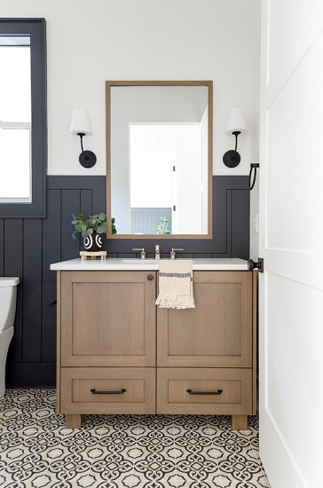 An image of a small bathroom with a blond wood v anity, 3/4 dark blue-gray paneling, and a pair of black metal sconces with white shades to either side of the mirror