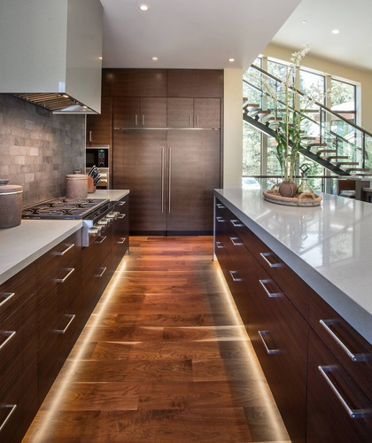 An image down the length of a kitchen, highlighting the toe-kick lighting along the base of the cabinets and kitchen island