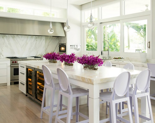 An image of a cheerful white kitchen with stainless steel appliances that are lit from the inside