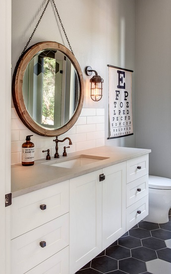 An image of a bathroom with a nautical-feeling wood mirror and matching factory-style sconce