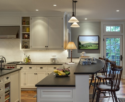An image of a low-lit kitchen in the evening, with a table lamp casting a cozy glow on the peninsula-island