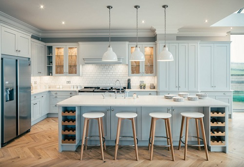 An image of a light colored kitchen, the counters and glass-fronted cabinets lit with a warm, cheery light