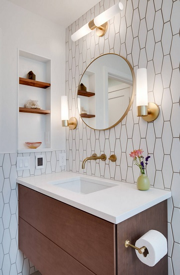 A small bathroom lit by two modern cylindrical sconces and a matching bar above the mirror
