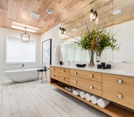 An image of a long bathroom with multiple sconces mounted into the mirror above the vanity