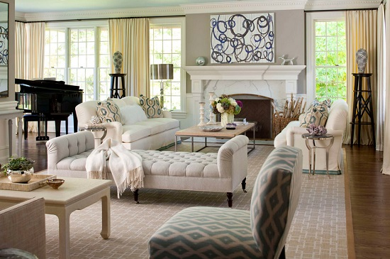 An image of a transitional living room. An elegant cream colored chaise divides the living room from a second seating area in the foreground
