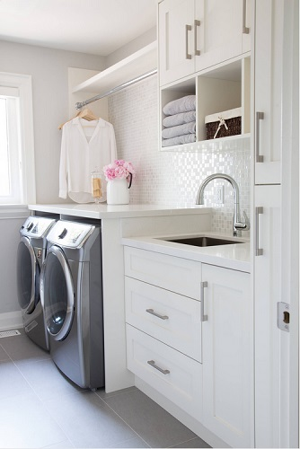 An image of a white laundry room with a gunmetal gray side-by-side washer and drier set.
