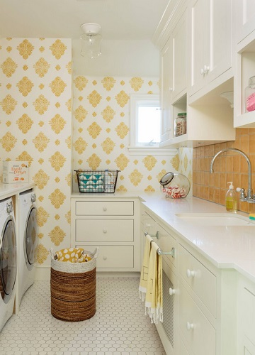 An image of a laundry room with cheerful yellow tile and wallpaper. The towels are a matching shade, and there is a wicker laundry basket full of more yellow linens in the center of the room.