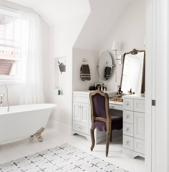 An image of a white bathroom. The makeup vanity is accessorized with a bold antique chair and mirror
