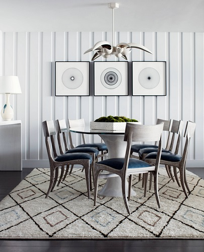 An image of a dining room done in shades of blue and silver, with a set of eight matching silver-and-blue chairs