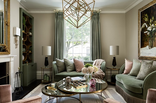 An image of a small but upscale traditional living room. The nesting coffee tables in the center are mirrored and gold, enhancing the glamorous feel of the space