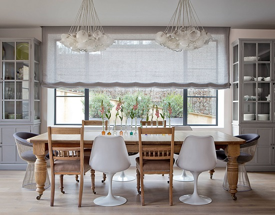 An image of a modern farmhouse style dining room. The chairs alternate between classic ladderbacks and modern white tulip chairs