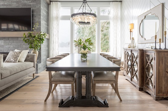 An image focused on the dining area in an open greatroom. The dining chairs are all pushed in, and are only slightly taller than the table itself, keeping line of sight clear to the sitting area beyond