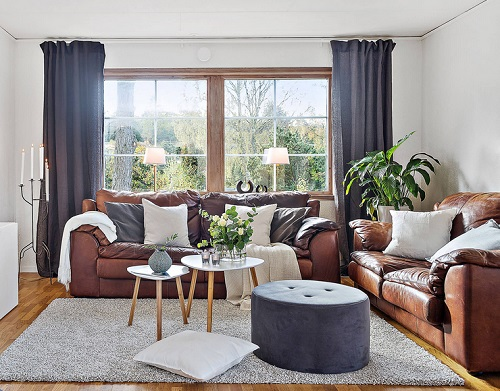 An image of a casual scandanavian style living room. Two conventional nesting tables are paired with an upholstered round ottoman to create a three-tiered coffee table
