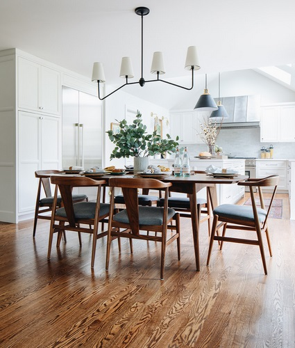 An image of a dining set centered between the kitchen and living areas of a greatroom. The table and dining chairs are walnut, with a distinctly midcentury style