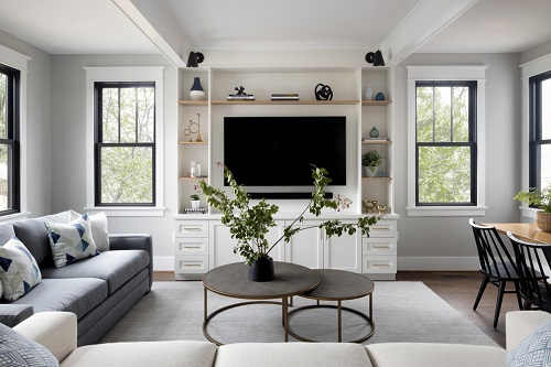 An image of a living room enclosed by a sectional sofa in the foreground and a dining table on the right. In the middle are two rounded coffee tables, un-nested to create a subtly tiered apperance