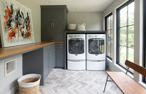 And image of a laundry room with striking marble flooring, arranged in a herringbone pattern.