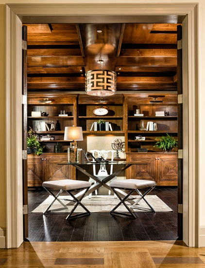 A bold home office done in assertive wood tones. The glass top of the desk is almost invisible, leaving the chrome legs appearing dramatic and sculptural.