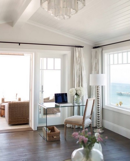 An image of a small home office setup in the corner of a large living room. An acrylic desk is set up in front of the patio door, preserving most of the view outside.