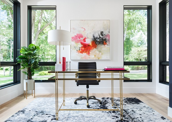 An image of a brightly lit home office. A gold and glass desk stands prominently in the center of the room, offset by the white walls behind it.