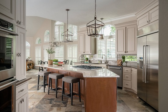 An image of a sunny, mediterranean kitchen iwth a gas cooktop in the center of the island